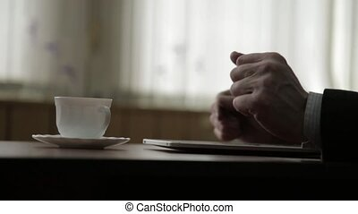 Man using tablet PC and drinking coffee. Close-up hands on a window background