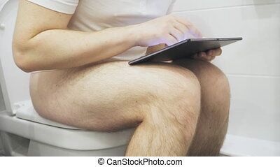 Man using tablet pc in the toilet.