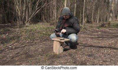 Man using tablet PC near birdhouse