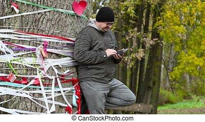 Man using tablet PC near the tree