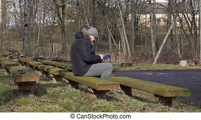 Man using tablet PC on bench