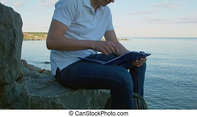 man using tablet pc on the rock outdoor