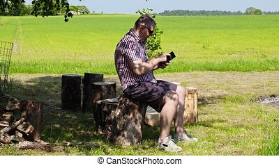 Man using tablet PC under the tree