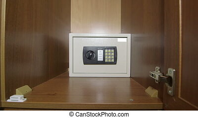 Man using the keypad of safe box mounted in wardrobe at home or hotel room