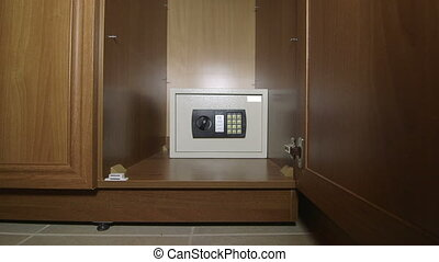 Man using the keypad of safe box mounted in wardrobe