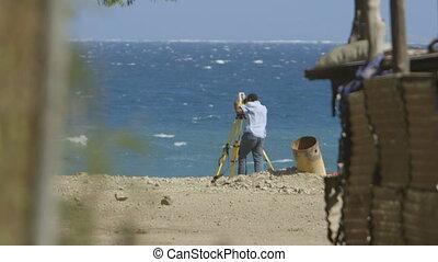 Man Using Theodolite on Beach - Steady, medium close up shot...