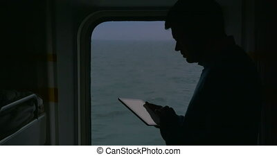 Man using touch pad during the cruise - Sihouette of a man...