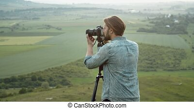 Man using tripod and camera for shooting nature from hill - ...