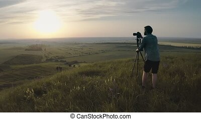Man using tripod and camera for shooting sunset on hill - ...