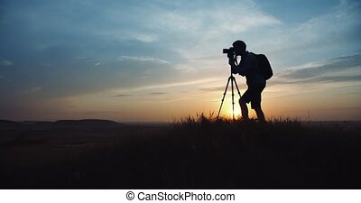 Man using tripod with digital camera for shooting sunset - ...