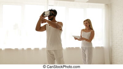 Man using virtual reality glasses woman holding digital tablet computer 3d technology concept, mix race couple home play video game smile
