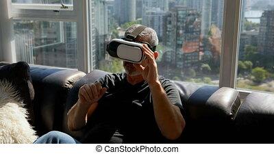 Man using virtual reality headset on sofa 4k