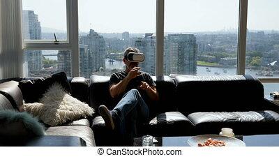 Man using virtual reality headset on sofa 4k - Man using...
