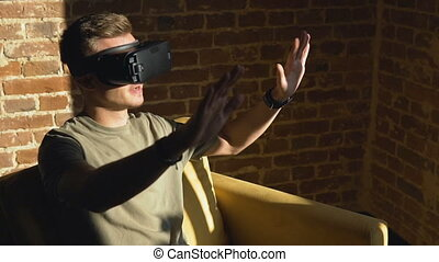 Handsome caucasian man uses a virtual reality helm in his yellow armchair, new experience, slow motion
