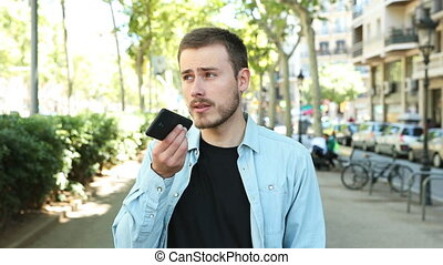Man using voice recognition on phone to record a message -...