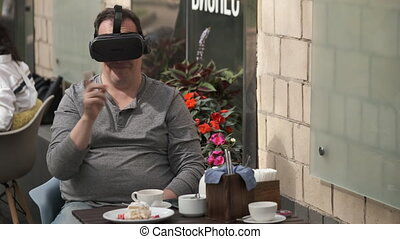 Curious male sitting at table on terrace of cafe and experiencing virtual reality in VR goggles while entertaining at weekend