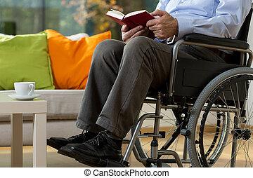 Man using wheelchair - Close-up of man using wheelchair...