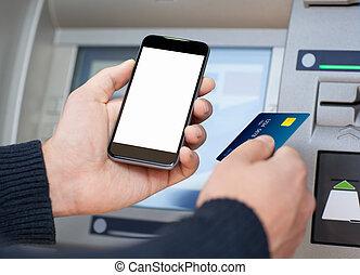 man, vasthoudende telefoon, en, een, kredietkaart, op, een, pinautomaat