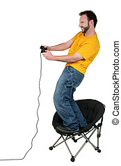 Man Video Games - Thirty year old man standing on chair with...
