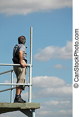 man viewing clouds from airfield observation platform