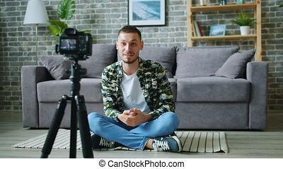 Man vlogger recording video for blog talking gesturing using...