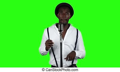 Man vocalist sings into a microphone and dance. Green screen. Slow motion