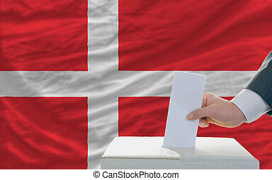 man voting on elections in denmark - man putting ballot in a...