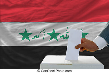 man voting on elections in iraq in front of flag