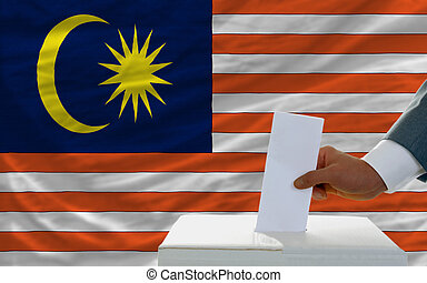 man voting on elections in malaysia in front of flag