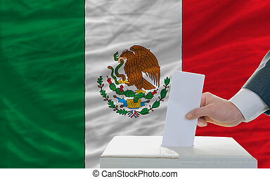 man voting on elections in mexico in front of flag
