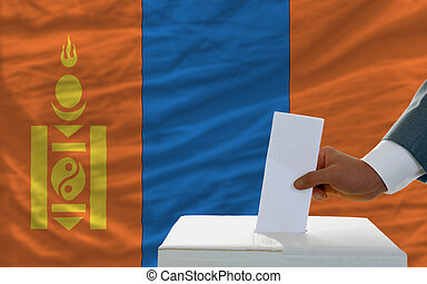 man voting on elections in mongolia in front of flag