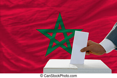 man voting on elections in morocco in front of flag