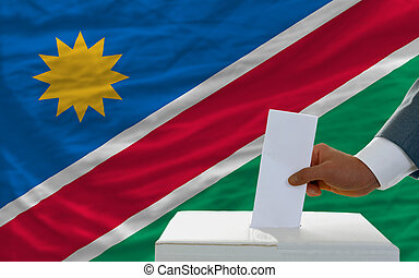 man voting on elections in namibia in front of flag