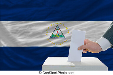 man voting on elections in nicaragua in front of flag - man...
