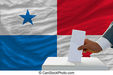 man voting on elections in panama in front of flag