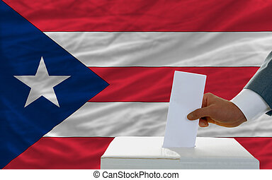 man voting on elections in puertorico in front of flag