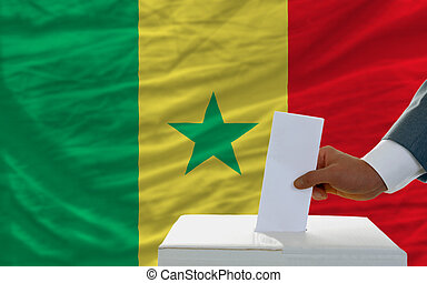 man voting on elections in senegal in front of flag