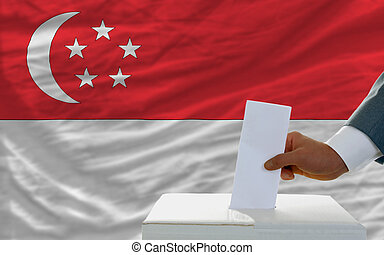 man voting on elections in singaporel in front of flag