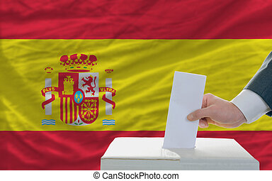 man voting on elections in spain in front of flag