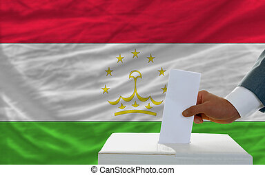 man voting on elections in tajikistan in front of flag