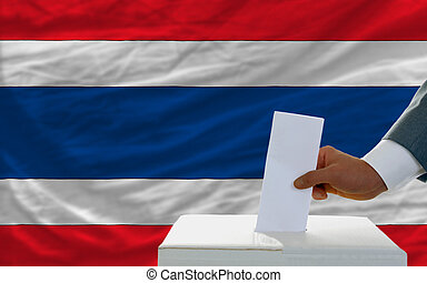 man voting on elections in thailand in front of flag
