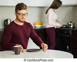 Man waiting for food on a kitchen at home