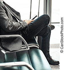 man waiting for his flight at the airport and looking at a mobile phone