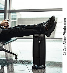 man waiting for his flight at the airport, legs on a suitcase and looking at a mobile phone
