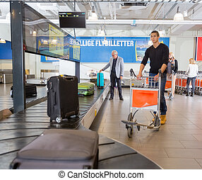Man Waiting For Luggage From Conveyor Belt At Airport