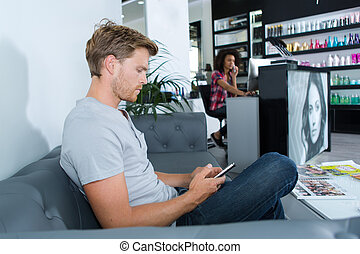 man waiting on a couch at the hairdressing salon