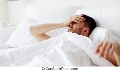 man waking up in bed at home - hangover, sleeping and people...