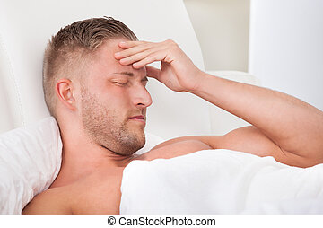Man waking up with a nasty headache from overindulgence or illness wincing in pain and raising his hands to his head