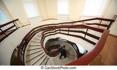 Man walk down by marble circular stairs, view from above