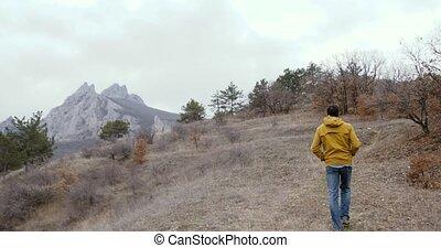 Man walk to rocks and mountains.